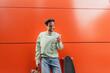 Leinwandbild Motiv cheerful man in sweatshirt holding backpack and using smartphone near longboard and orange wall.