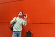 Leinwandbild Motiv cheerful man in sweatshirt holding smartphone with blank screen and waving hand near orange wall.