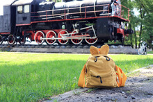 The Concept Of Summer Travel By Rail. Yellow Backpack On The Background Of An Old Steam Locomotive On A Sunny Summer Day, Close-up