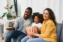 Fun Family With Little Daughter Are Watching Comedy Movie Together And Eating Popcorn From A Large Striped Bucket At Cozy Home