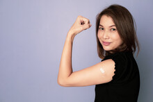 Portrait Of Vaccinated Asian Woman Showing Plaster Band Aid On Arm And Show Fist Punch In Winning And Trust Sign After Coronavirus Vaccine Injection Look At Camera. Getting Vaccination Concept.