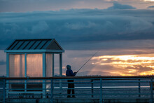 A Silhouette Of A Person Fishing Off Of A Pier At Sunset On An Overcast Day