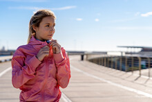 Thoughtful Woman Holding Jacket Zipper While Looking Away