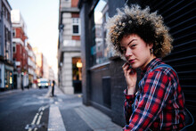 Curly Haired Young Woman In Front Of Shutter