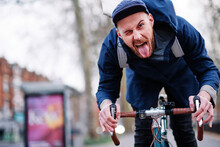 Young Man Sticking Out Tongue While Riding Bicycle