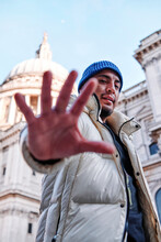 Young Man In Padded Jacket Gesturing While Standing By St. Paul Cathedral, London, UK