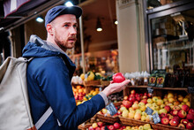 Young Man Looking Away While Holding Apple At Fruit Shop