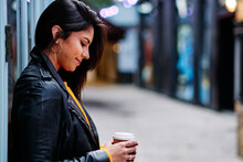 Smiling Woman With Disposable Coffee Cup Leaning On Wall