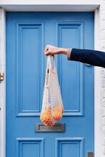 Man Holding Bag Of Oranges Outside Blue Door