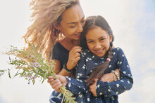 Happy Mother And Daughter With Bunch Of Wildflowers