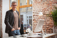 Mature Male Professional With Hands In Pockets Standing By Desk At Work Place