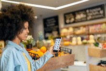 Afro Woman Using Mobile Application In Grocery Store