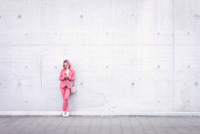 Woman In Smart Casual Using Mobile Phone In Front Of Concrete Wall