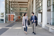 Male And Female Colleagues Talking While Walking On Footpath