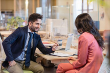 Smiling Male Professional Offering Pen To Female Entrepreneur While Sitting At Desk In Coworking Office