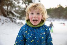 Blond Hair Boy In Snow During Winter