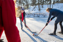 Senior Man Playing Ice Hockey With Friends On Snow During Winter