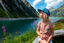 Girl Wearing Cap Looking At View While Sitting On Wooden Bench By Lake At Zillertal, Austria