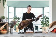Female Chef Adjusting Meat On Ham In Restaurant