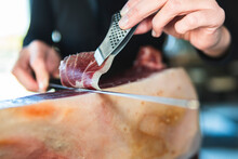 Young Female Chef Cutting Slice Of Ham With Kitchen Knife