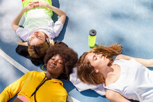 Female Friends Lying Together On Sports Court Floor