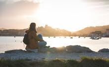 Spain, Cantabria, San Vicente De La Barquera, Young Backpacker Tourist Enjoying Sea Coast At Sunset