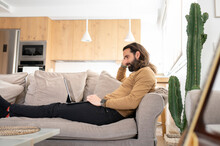 Man With Long Hair Using Tablet PC While Relaxing On Sofa At Home