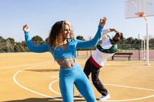Smiling Woman Dancing With Friend On Basketball Court