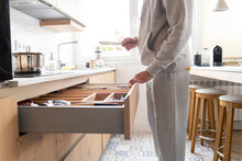 Man Opening Drawer In Kitchen At Home