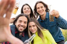 Happy Friends Showing Beer Bottles In Front Of Sky