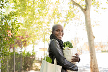 Smiling Woman With Shopping Bag Carrying Vegetables On Sunny Day