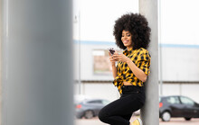 Woman Using Mobile Phone While Leaning On Pole