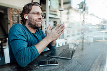 Smiling Manwith Hands Clasped By Laptop In Cafe