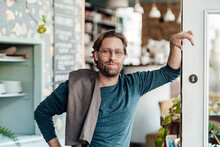Male Owner Leaning On Door In Coffee Shop