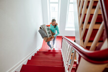 Young Woman Carrying Cardboard Boxes While Moving Up On Staircase At Home