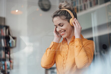 Happy Female Owner Listening Music Through Headphones A Cafe