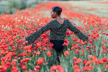 Mid Adult Woman Touching Flowers In Poppy Field