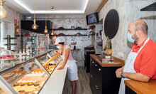 Male Owner Wearing Face Mask Looking At Woman Arranging Pastry In Retail Display At Bakery