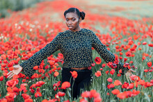 Woman With Arms Outstretched Standing In Poppy Field