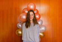 Smiling Woman Standing By Wall With Balloons Decoration At Home