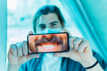 Young Man Showing Toothy Smile On Mobile Phone During Covid-19