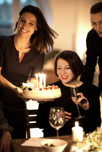 Beautiful Woman Looking At Birthday Cake Held By Female Friend During Celebration At Home
