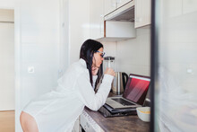 Sensual Female Professional Using Laptop In Kitchen While Working At Home
