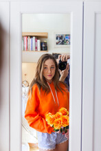 Young Woman With Orange Flowers Looking In Mirror While Man Photographing Through Camera In Background