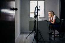 Female Fashion Model Recording Through Mobile Phone At Studio