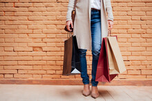 Woman Holding Shopping Bags While Standing In Front Of Brick Wall