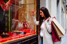 Woman With Shopping Bags While Window Shopping