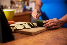 Woman Cutting Zucchini On Wooden Board In Kitchen