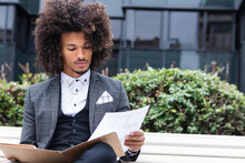 Young Male Entrepreneur Examining Documents In File While Sitting On Bench