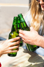 Male And Female Friends Toasting Beer Bottles At Bar